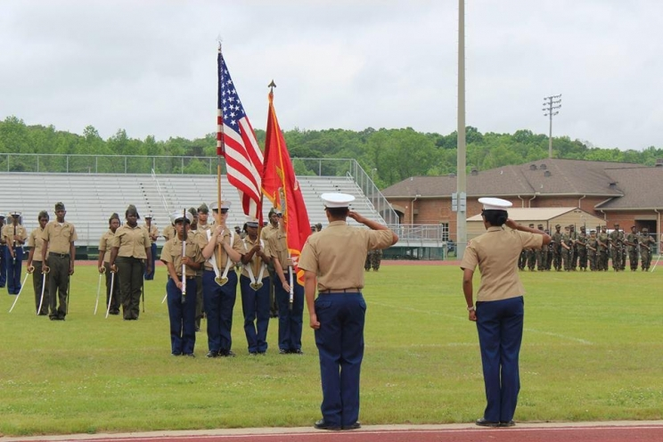 Paul W. Bryant High School Marine Corps JROTC cadets stand in formation on the school's football field while the colors are presented.