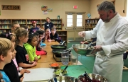 Faucett-Vestavia Elementary School 4th graders watch Levee Executive Chef Kurt Jones prepare the fresh ingredients for the collard roll-ups.