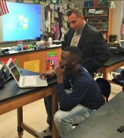 Tuscaloosa City Schools Assistant Superintendent, Dr. Mike Daria, watches as Junior, James Dent, takes an assessment on a school-provided Chromebook at Paul W. Bryant High School.